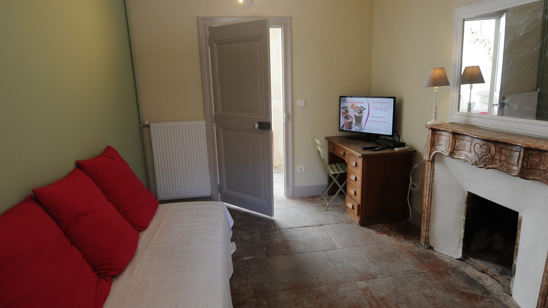 Little living room with TV & single bed - view on the corridor & terrace